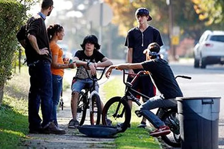 Young people on BMX bikes talk together after visiting a shrine for Autumn Pasquale Wednesday, Oct. 24, 2012, in Clayton, N.J., near where the missing 12-year-old girl's body was found in a home's recycling bin. (AP Photo / Mel Evans)