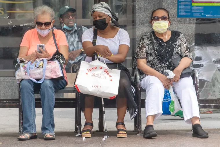 Three unidentified women wear their face masks at a bus stop on Broad Street in July.