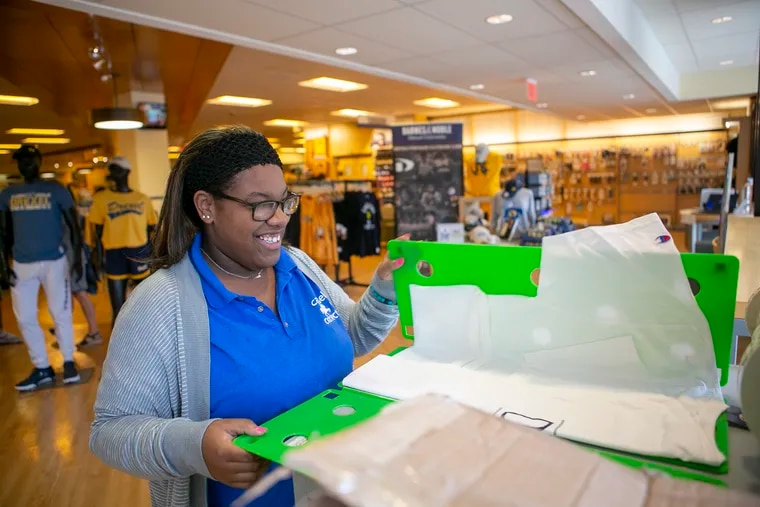 Hannah Scott, 19, folds T-shirts during her Project SEARCH internship at the Barnes & Noble bookstore on Drexel University's campus.