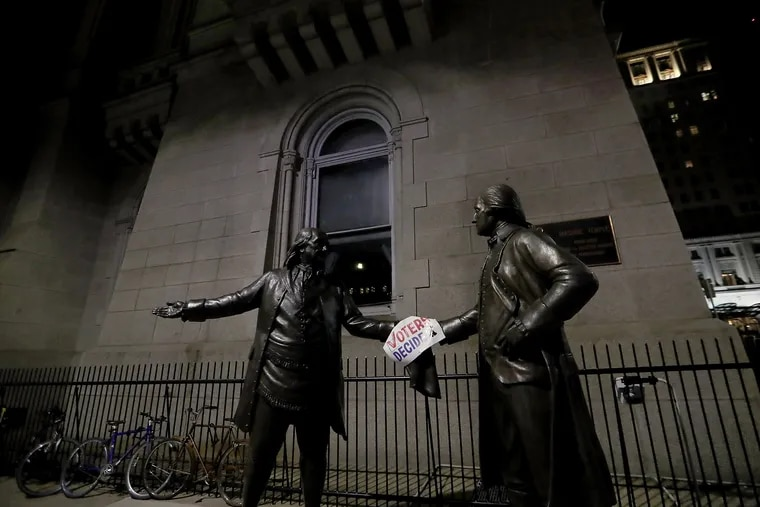 """Statues of national heroes Benjamin Franklin, left, and George Washington hold a sign that says """"Voters Decide"""" in Philadelphia on Saturday."""