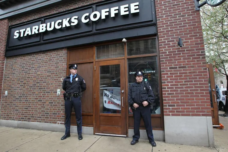 Police officers stand Monday outside the Starbucks at 18th and Spruce Streets where two black men were arrested.