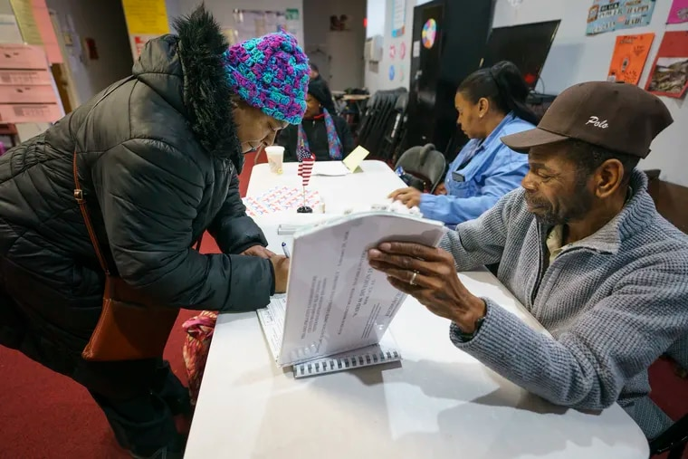 Denise King (left) signs in with Robert Kelly (right), majority inspector, at a polling place at Antioch Universal Church on North 52nd Street in Philadelphia on Tuesday.