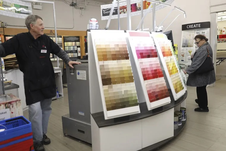 Rich Jurewicz, left, a paint specialist at Village True Value Hardware store in Western Springs, Ill., waits to assist customers.