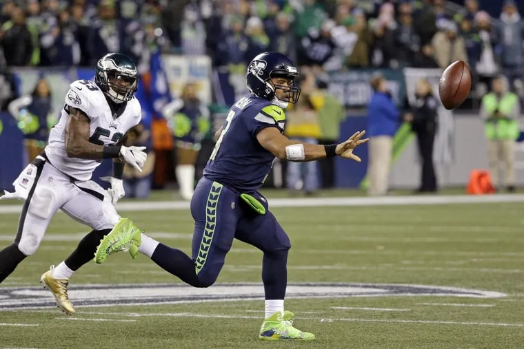 Seattle Seahawks quarterback Russell Wilson, right, shovels the ball on the run as the Eagles' Nigel Bradham moves in.