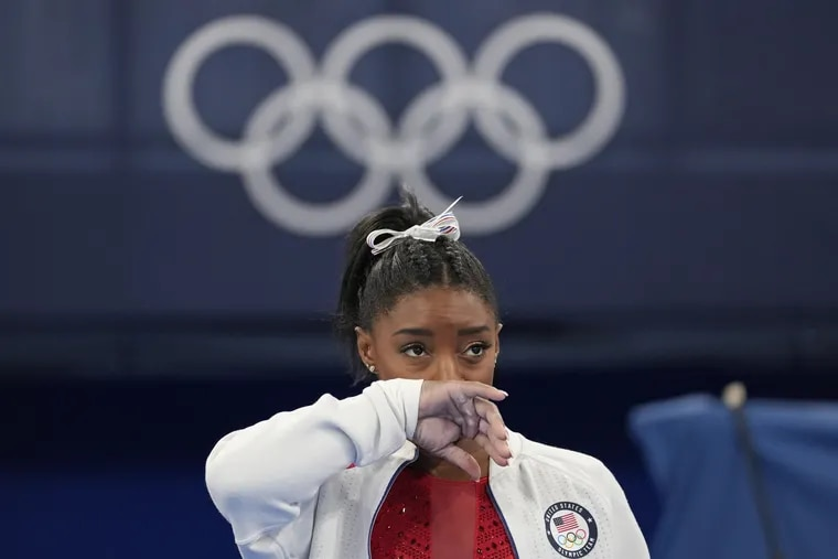 Simone Biles, of the United States, watches gymnasts perform after she exited the team finals at the 2020 Summer Olympics.