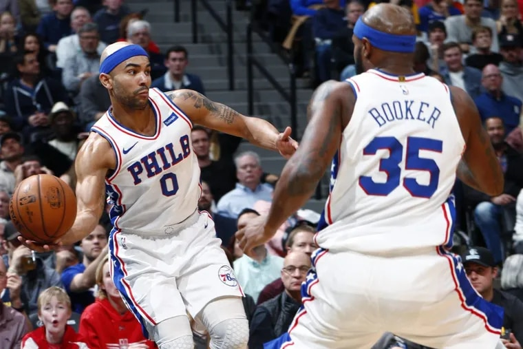 Sixers guard Jerryd Bayless reaches for a rebound near forward Trevor Booker during the team's win against the Denver Nuggets on Saturday.