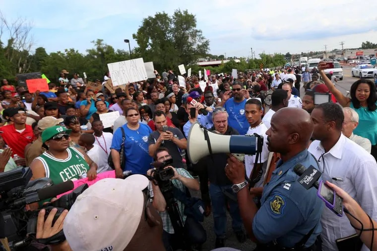 Missouri State Highway Patrol Capt. Ronald Johnson addresses the crowd of protesters, asking them to stay on the sidewalk and not block traffic Thursday, Aug. 14, 2014, in Ferguson, Mo. The Missouri Highway Patrol seized control of a St. Louis suburb Thursday, stripping local police of their law-enforcement authority after four days of clashes between officers in riot gear and furious crowds protesting the death of an unarmed black teen shot by an officer. (AP Photo/St. Louis Post-Dispatch, David Carson)