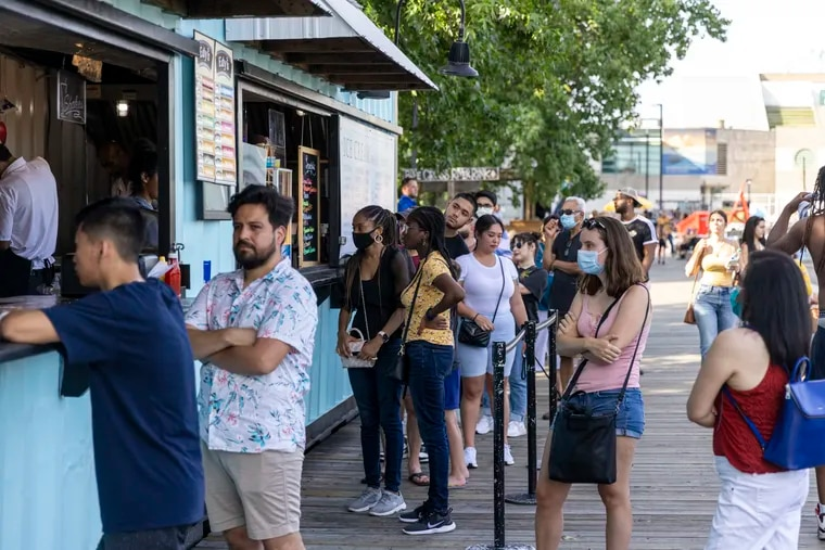 People with and without masks wait in line to order food and enjoy the weather at Spruce Street Harbor Park on Saturday. This is the first weekend of the city's new mask mandate.