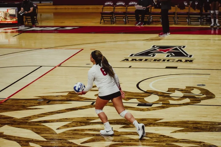 Temple sophomore libero Falanika Danielson prepares to serve during a volleyball match.
