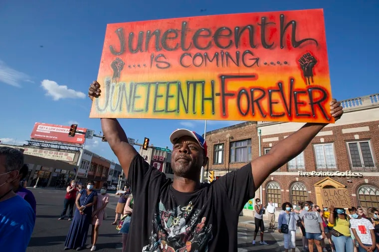 Rich Blye holds up a sign reminding those that Juneteenth, which commemorates the end of slavery in the United States, is approaching. He wants the event placed on the Upper Darby calendar.
