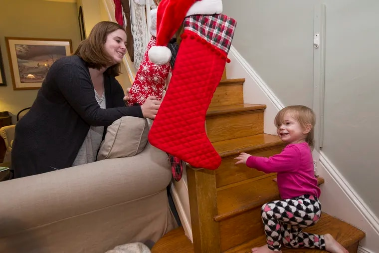 Megan Vargha, and Maggie, 18 months, play peek-a-boo around the Christmas stockings on Dec. 21, 2018.