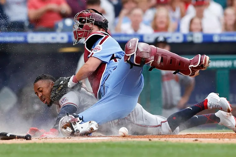 Atlanta Braves second baseman Ozzie Albies slides safely into home plate as the ball squirts away from Phillies catcher Andrew Knapp in the first inning Thursday night at Citizens Bank Park.