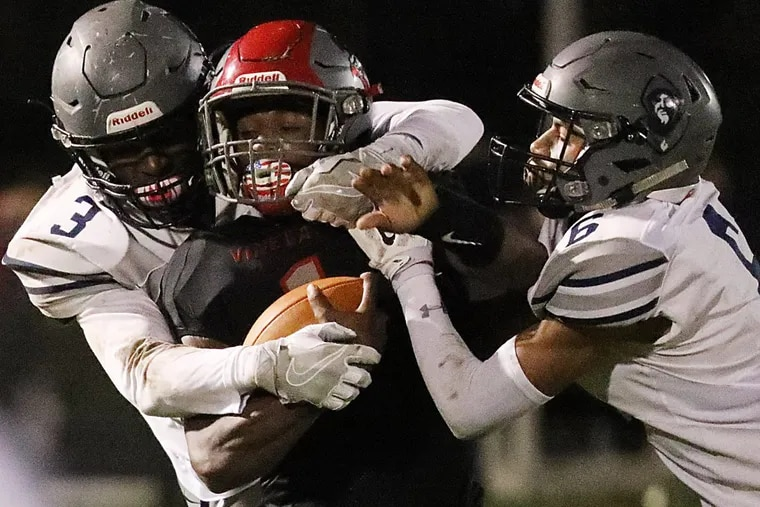 Vineland QB Isaih Pacheco is tackled by St. Augustine's Xavier File (left) and Sincere Rhea.