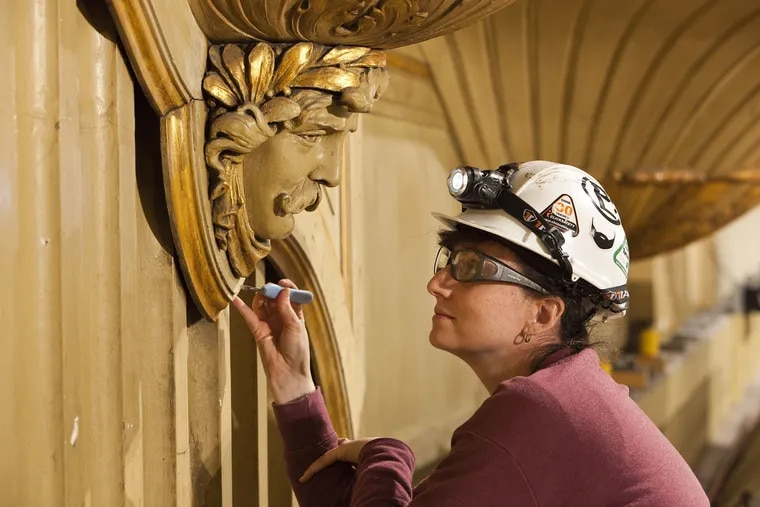A woman works on the facade of the Wanamaker Organ, recently restored at Macy's in Center City.