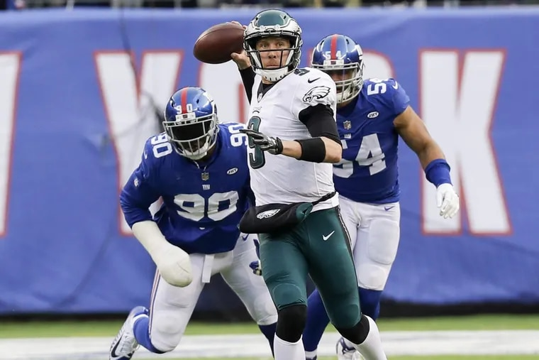 Eagles quarterback Nick Foles throws the football past New York Giants defensive end Jason Pierre-Paul (left) and defensive end Olivier Vernon during the third-quarter on Sunday, December 17, 2017. YONG KIM / Staff Photographer