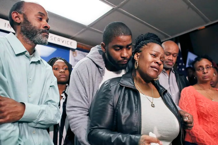 Family members surround Keisha Gaither, third from left, mother of kidnapping victim Carlesha Freeland-Gaither, during a news conference in Philadelphia on Tuesday, Nov. 4, 2014.  (AP Photo/ Joseph Kaczmarek)