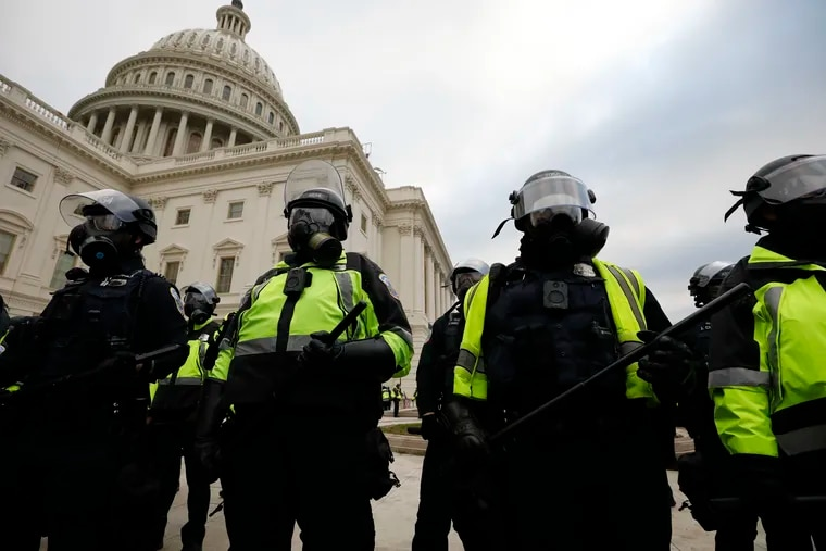 Police officers in riot gear stand guard while supporters of President Donald Trump protest on the steps of the U.S. Capitol Building on Capitol Hill in Washington, D.C., on Wednesday, Jan. 6, 2021.