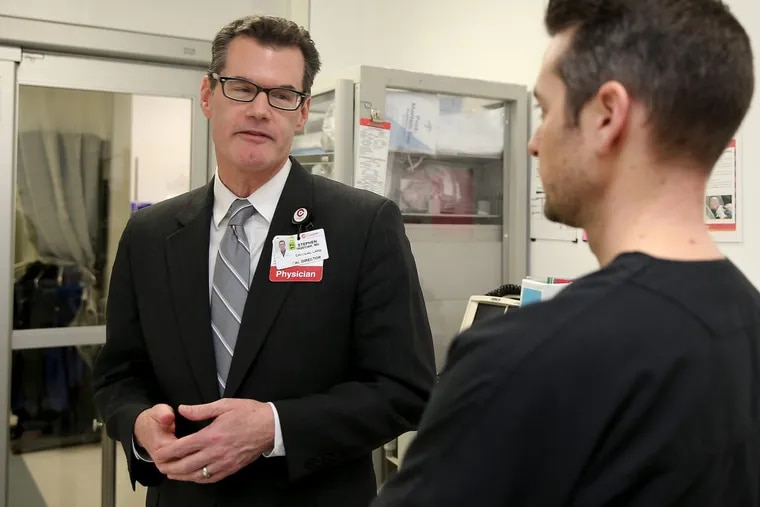 Stephen Trzeciak, a critical care doctor, and  Brian Roberts, right, an emergency physician, talk at Cooper University Hospital, where both work.  They are studying how compassion affects health care.