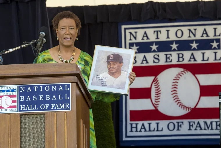 Former Inquirer sports columnist Claire Smith holds up a painting of former player Don Baylor — painted by her father — as she gives her acceptance speech after receiving the J.G.Taylor Spink Award from the Baseball Hall of Fame.