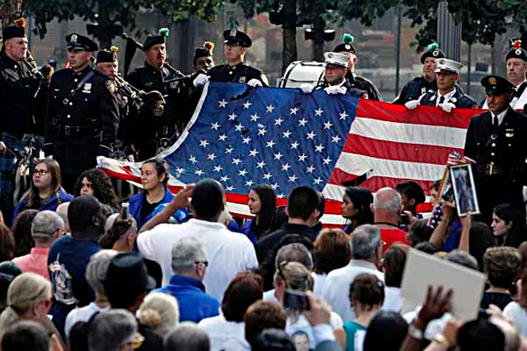 The World Trade Center Flag is presented as friends and relatives of the victims of the 9/11 terrorist attacks gather at the National September 11 Memorial at the World Trade Center site, Wednesday, Sept. 11, 2013, for a ceremony marking the 12th anniversary of the attacks in New York. (AP Photo/Jason DeCrow)