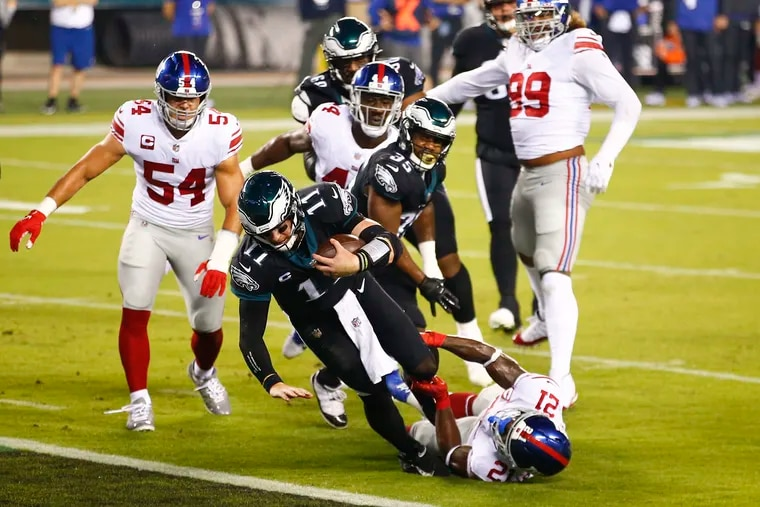 Eagles quarterback Carson Wentz dives into the end zone for a first-quarter touchdown past New York Giants safety Jabrill Peppers on Thursday.
