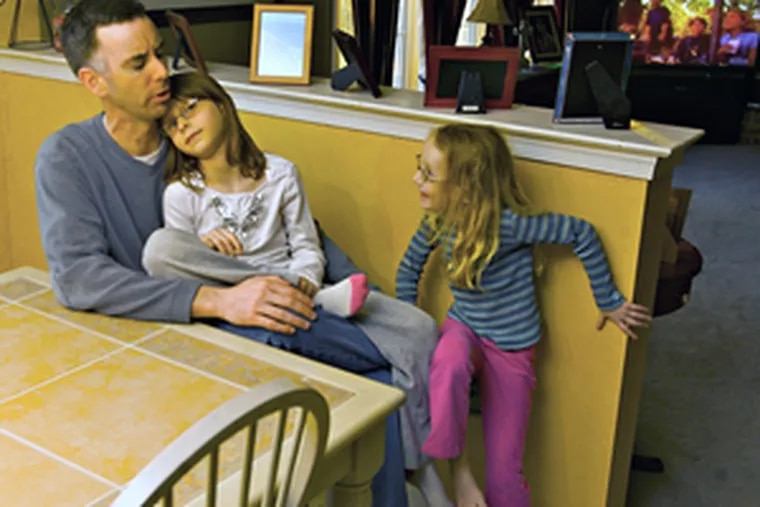 """Brian McCausland with two of his four daughters at their Pennsburg home. In real estate parlance, families like his """"drive to qualify"""" for a mortgage."""