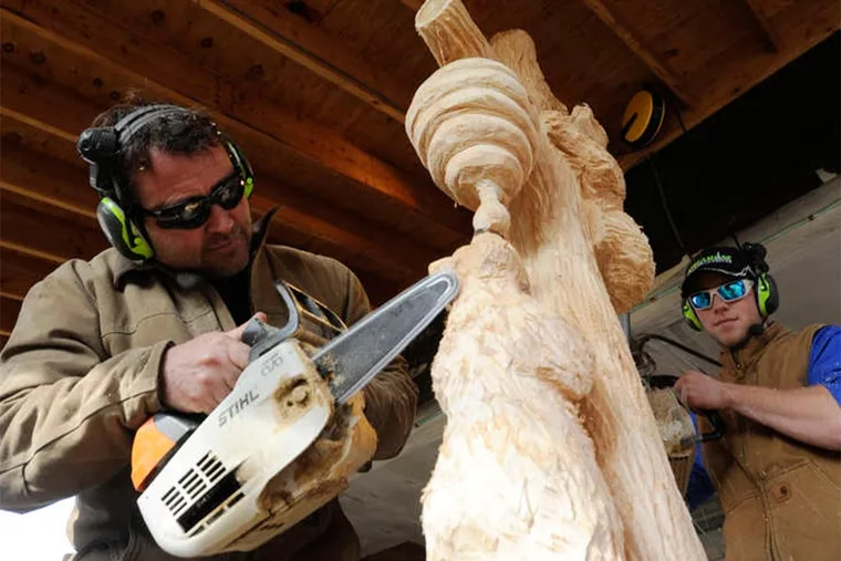 Wood Carver Marty Long, left and his Assistant Carver Jaz Katz, right, are shown at his Phoenixville, Pa. shop crafting a commisioned chainsaw art work Sunday Nov. 27, 2016.