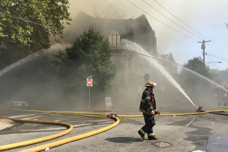 Firefighters battle a blaze at the Good Shepherd Presbyterian Church on Lansdowne Avenue in Overbrook on Monday morning.