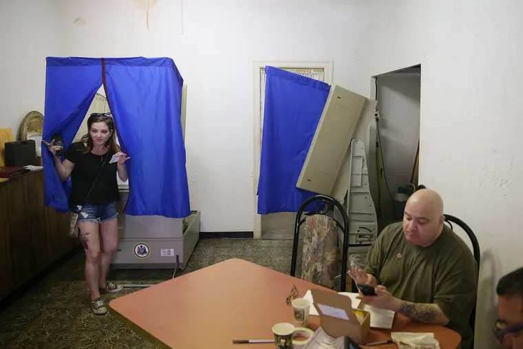Kym Rosen, left, exits a voting booth at a polling place near 7th and Wolf streets in South Philadelphia during the Pennsylvania primary election on Tuesday, May 15, 2018.