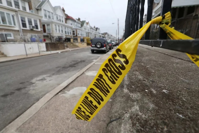 Philadelphia police crime scene tape remains tied to a porch rail along the 6600 block of Dorel St in Southwest Philadelphia on Friday morning December 22, 2017. Four people were shot, one died late Thursday evening.