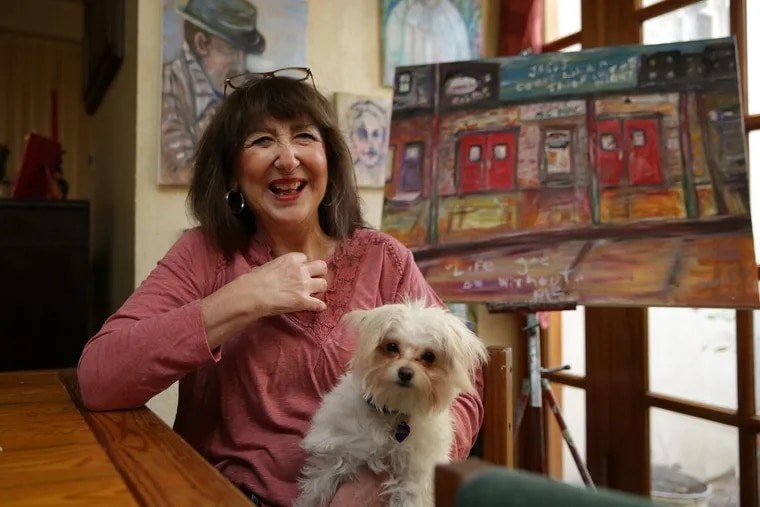 Connie Tartaglia talks about her paintings while holding her dog, Puddles. Her son Joseph died of cancer a few years ago. Her paintings will be part of a benefit to raise money for cancer research.
