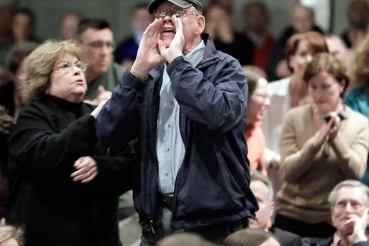 Mary Alice Walsh tries to stop her husband, Larry Walsh of Haddonfield, from yelling and interrupting developer J. Brian O'Neill as he speaks to the public during a meeting at Haddonfield High School on April 22, 2015. (ELIZABETH ROBERTSON/Staff Photographer)