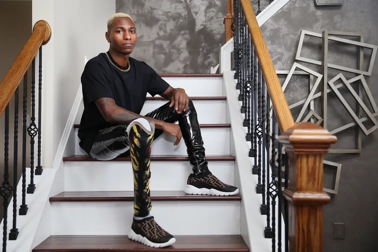 Reef Hall sits for a portrait to show off a snakeskin design on his prosthetic leg at his home in Williamstown, N.J., on Friday, March 6, 2020. In 1996, Hall was 4 years old when his foot was mangled by a malfunctioning SEPTA station escalator. He is now an aspiring model who designs vinyl wraps for his prosthetics.
