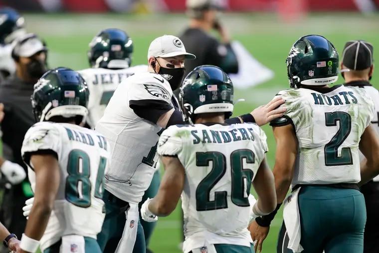 Eagles backup quarterback Carson Wentz taps Eagles quarterback Jalen Hurts after Hurts scored a touchdown against the Arizona Cardinals on Sunday.