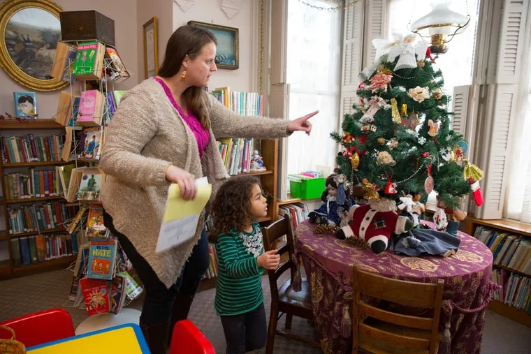 Meredith Rumer and daughter Bianca, 4, examine holiday decorations at the Ryerss Museum and Library in Philadelphia's Burholme Park. The house and its residents have played a role in local history.