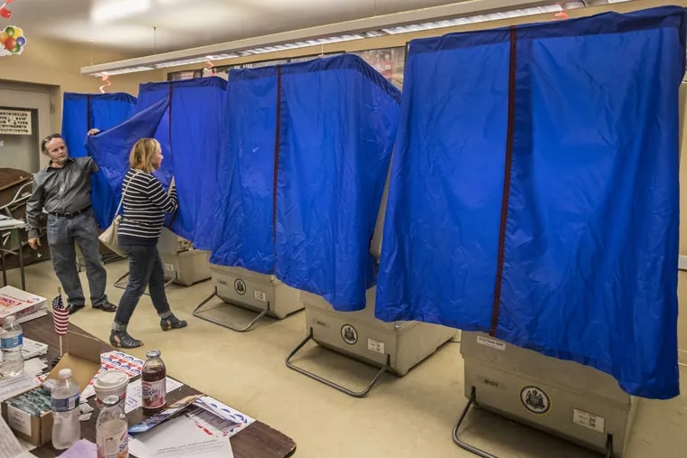 A voter enters a booth.