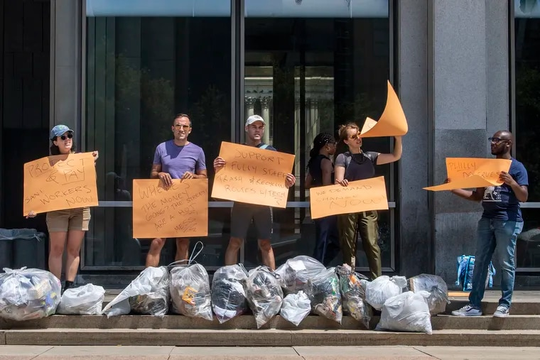 People protest with uncollected trash bags at the Municipal Services Building in Philadelphia, Pa. Wednesday, July 28, 2021.