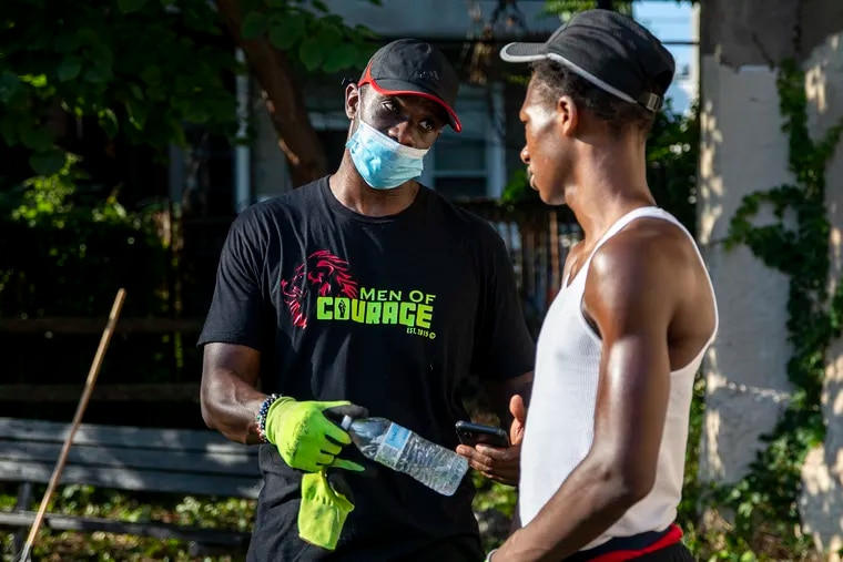 Taj Murdock (left), one of the main organizers with the Black Brotherly Love group, reaches out to Shakur Smith, 17, a volunteer, to talk about long-term goals and his career path during a cleanup event at the West Mill Creek Playground.