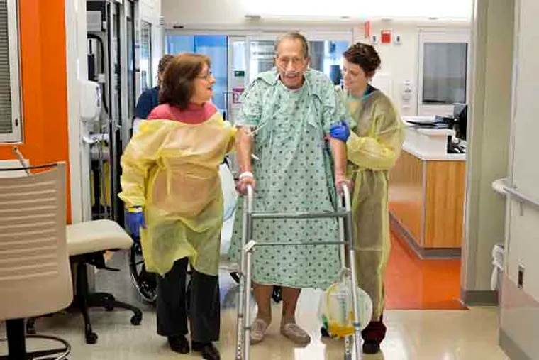 Nathan Maryn walks in the post-surgical intensive care unit at The Johns Hopkins Hospital with his wife, Barbara Maryn, and Jennifer Sahm, a physical therapist. A nurse followed with a chair in case he became unsteady. Exercise in the ICU is associated with better longterm outcomes. (Credit: Christopher Myers)