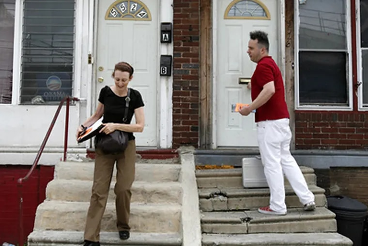 """Soliciting support and testimonials, Jane Golden and Steve Powers go door to door along Market Street near 56th. The program they're promoting, """"Love Letters,"""" will include a Web site where postings will include narratives by neighbors. (Eric Mencher / Staff Photographer)"""