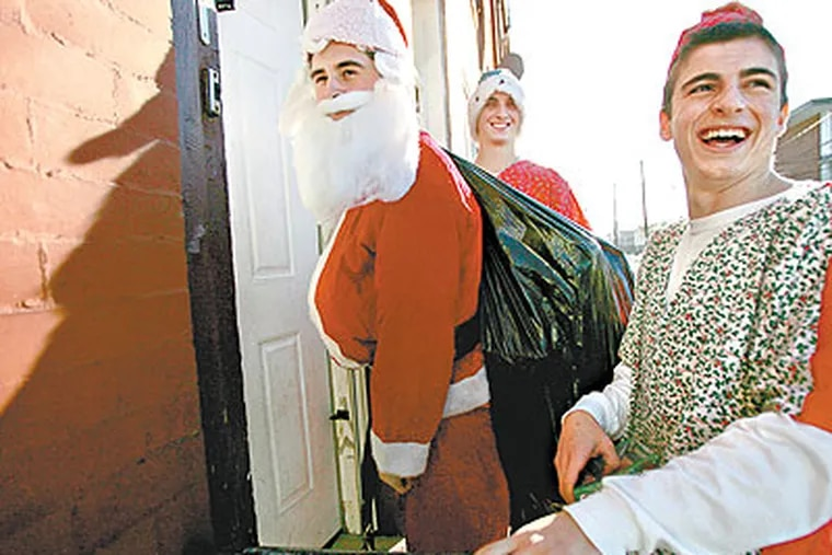 Michael DeFeo as Santa and his elves, Charles Foltz (middle) and Mark Casale (right), wait for an answer at a door on 22nd Street so they can deliver presents. (David Swanson / Staff Photographer)