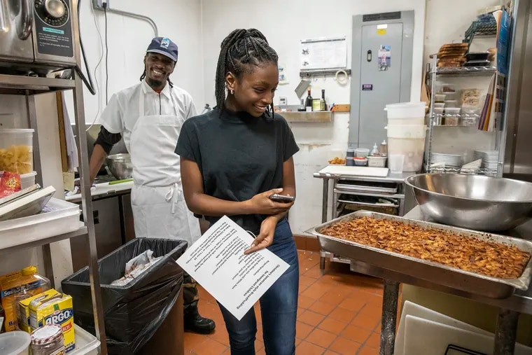Christine Thompson, 16, looks at the Jamaican-style bread pudding baked and unveiled by chef Damon Menapace (not pictured) in the kitchen of Le Virtu restaurant in South Philadelphia on Thursday, March 14, 2019. Thompson's parents are currently seeking sanctuary in the First United Methodist Church of Germantown. All proceeds from the bread pudding at the restaurant will go to the Thompson family.