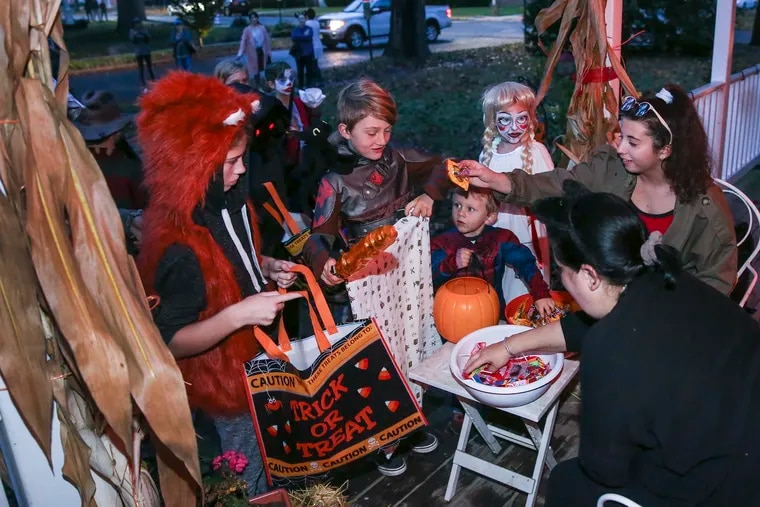 The Bova family hands out candy to costumed kids in Hammonton the night before Halloween. Town officials moved trick or treat because of Thursday's weather forecast.