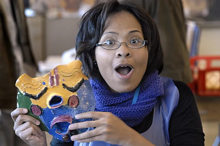 Dorothy Johnson, 17, holds up a mask she made while working with Claymobile, the outreach program of the Clay Studio, at Strawberry Mansion High School. Johnson will soon begin working for the Claymobile, assisting in after-school programs.