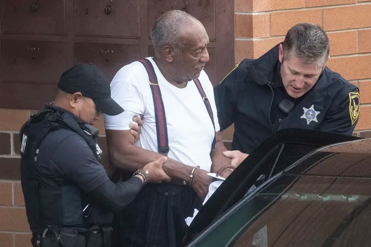 Bill Cosby is escorted by police in handcuffs as he exits the Montgomery County Correctional Facility in Norristown on Tuesday.