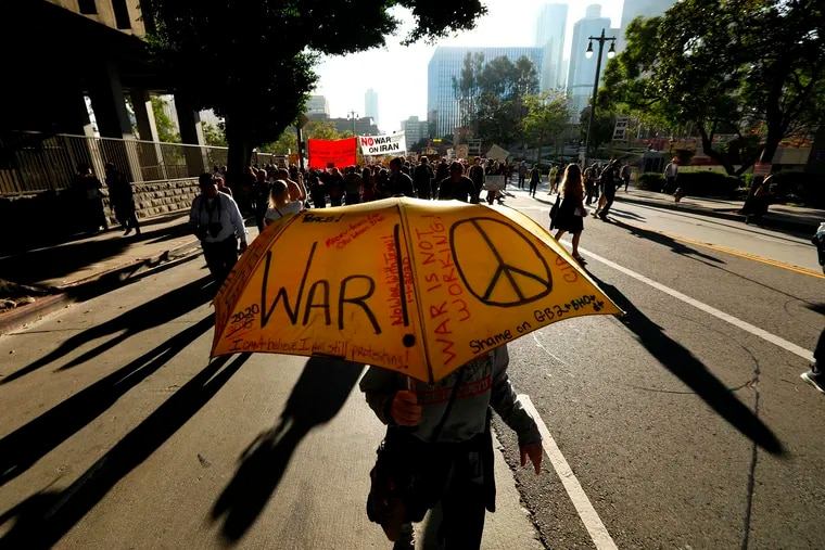 """Kathleen Schwartz's umbrella asks the question, """"war or peace,"""" while joining around 300 people taking part in a day of protest, voicing their opposition to war with Iran, in Los Angeles on Saturday."""