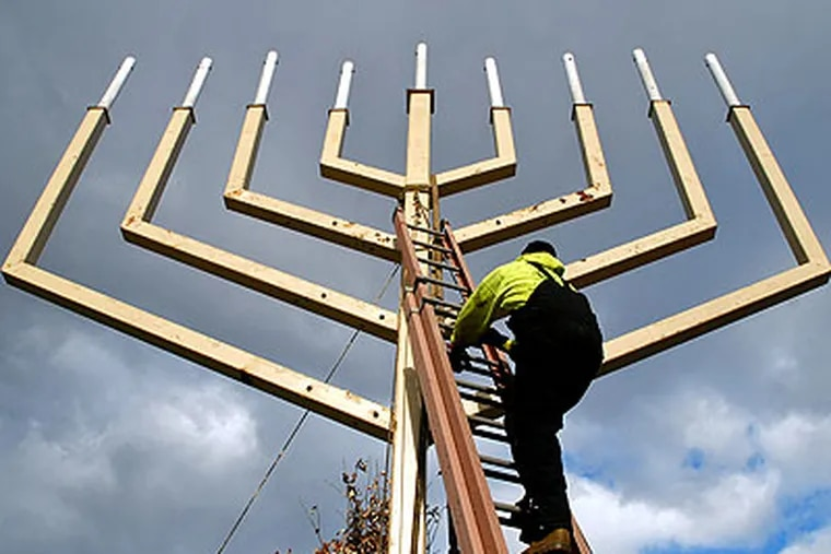 Brian Yohnnson of Moorestown unties the crane after he and co-workers from Mayberry Riggers installed the 37-foot-high menorah Thursday on Independence Mall, where it will be lit Friday evening to mark the first night of Hanukkah. (Tom Gralish / Staff Photographer)