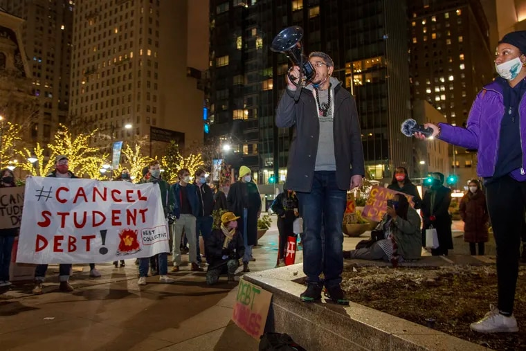 Ismael Jimenez, a social studies and African American studies teacher at Kensington Creative & Performing Arts High School, speaks with a megaphone at a Jan. 4 rally outside Biden campaign headquarters at 15th and Market Streets calling for student debt cancellation. Next to him is Lauren Horner (right) with the Debt Collective Union.