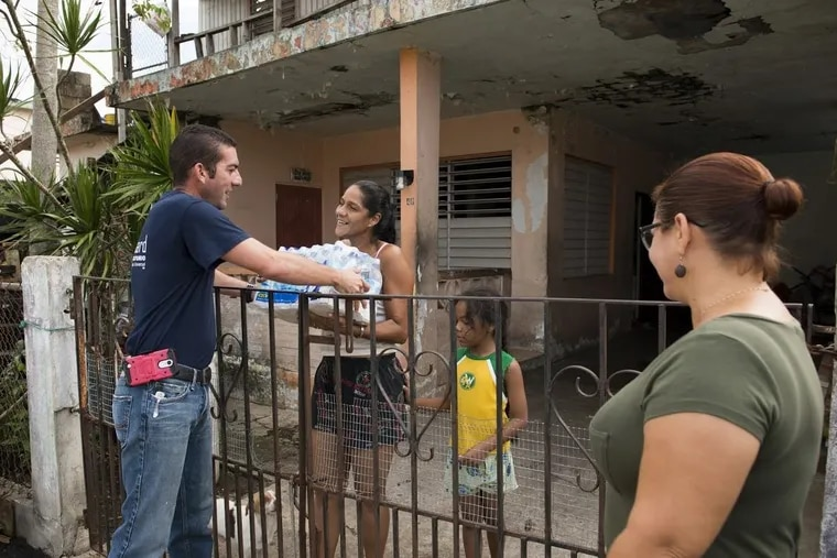 Jesús Pagán Torres (left) and Moriama Cortés (right) are part of a team of faculty and staff of Escuela Delia Dávila de Cabán who continue to distribute water and emergency relief in  neighborhoods still without power and water. Escuela Delia Dávila de Cabán has served as a distribution point for the Puerto Rico Recovery Fund's emergency relief efforts since it was established days after the storm.