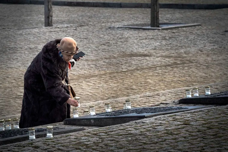 A Holocaust survivors places a candle on a monument at Auschwitz-Birkenau to remember those who were killed in the Holocaust. Hundreds of Holocaust survivors join delegates from around the world at Auschwitz-Birkenau, the former Nazi death camp, in Oświęcim, Poland, on January, 27, 2020, the 75th anniversary of the camps liberation and International Holocaust Remembrance Day.